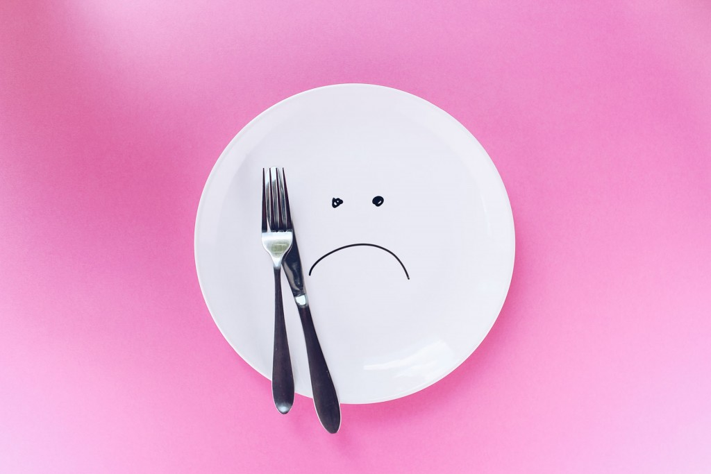 Plate with sad face on it, symbolizing an eating disorder caused by trauma