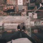 person standing on the edge of a tall building